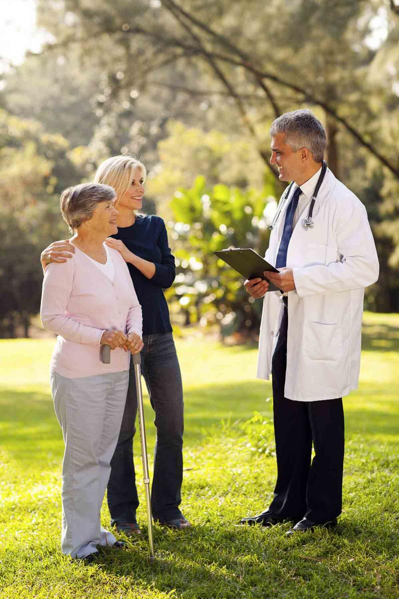 an older woman with her daughter stand outside with a male physician