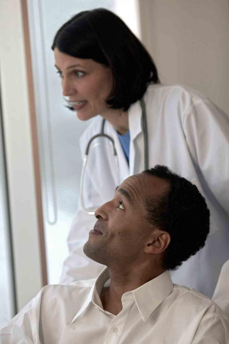 female doctor smiling and looking out of the window with male patient