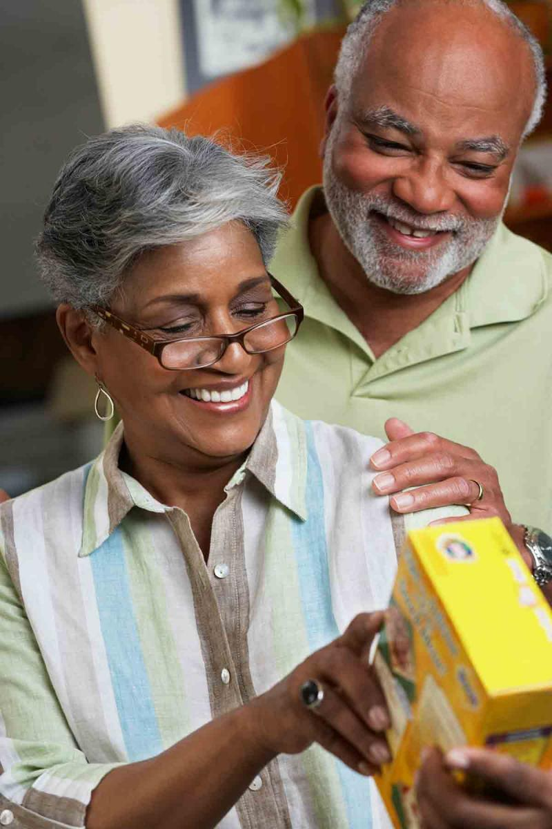 an older woman wearing glasses reads from the side of a box as her husband touches her shoulder
