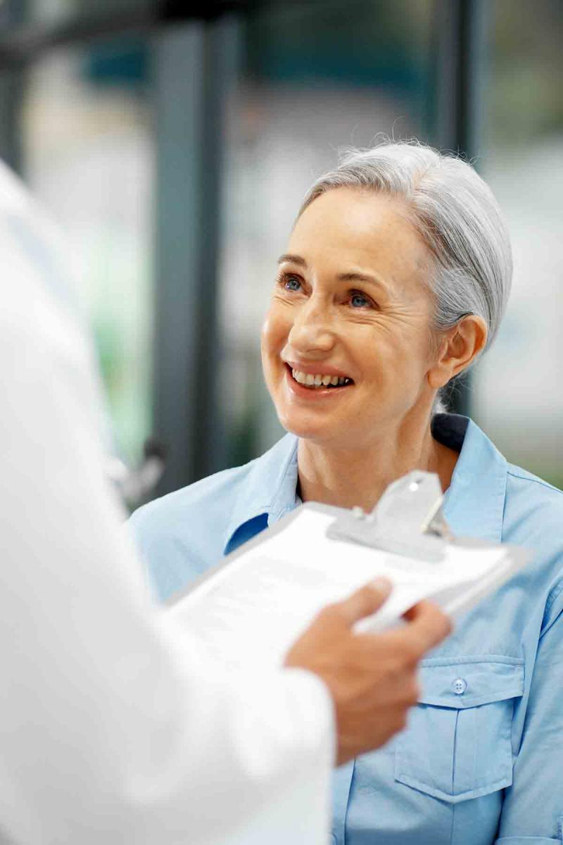 an older woman smiles as while speaking to a health care provider