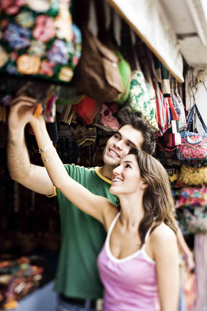 a young man and young woman shop together in an outdoor market