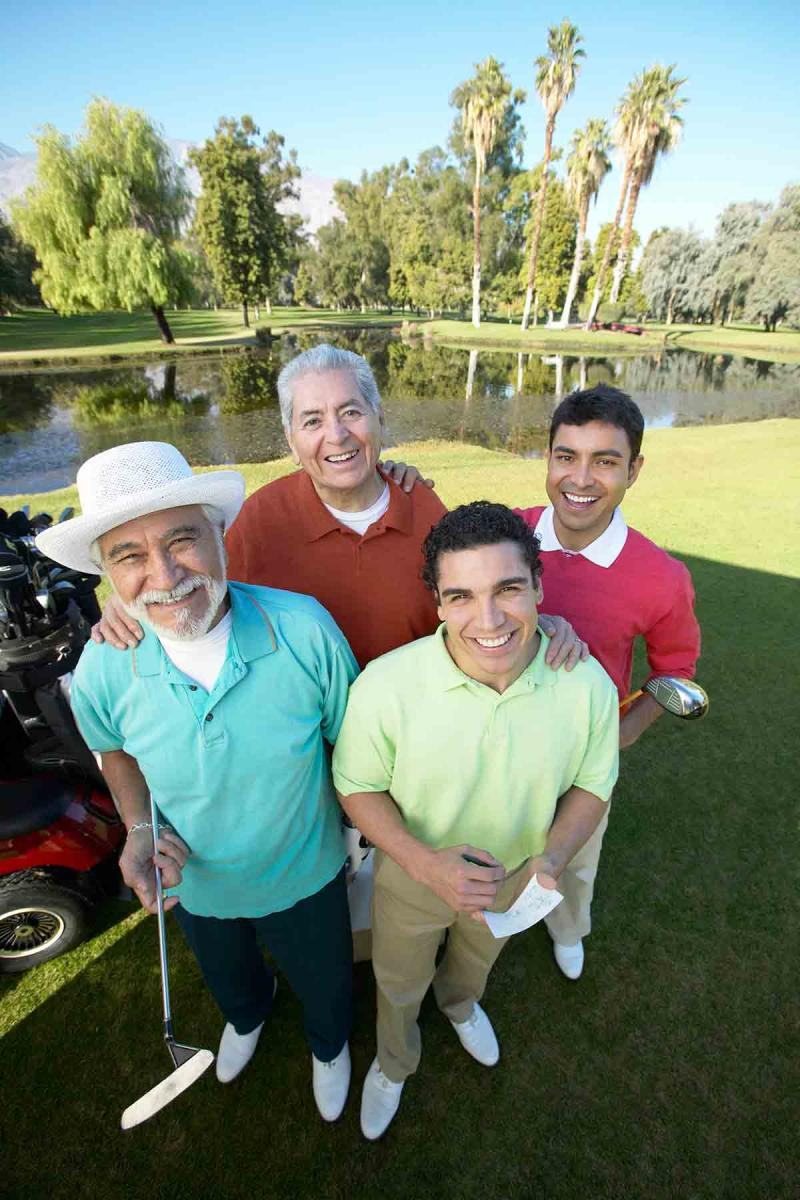 four men of different ages standing together on a golf course