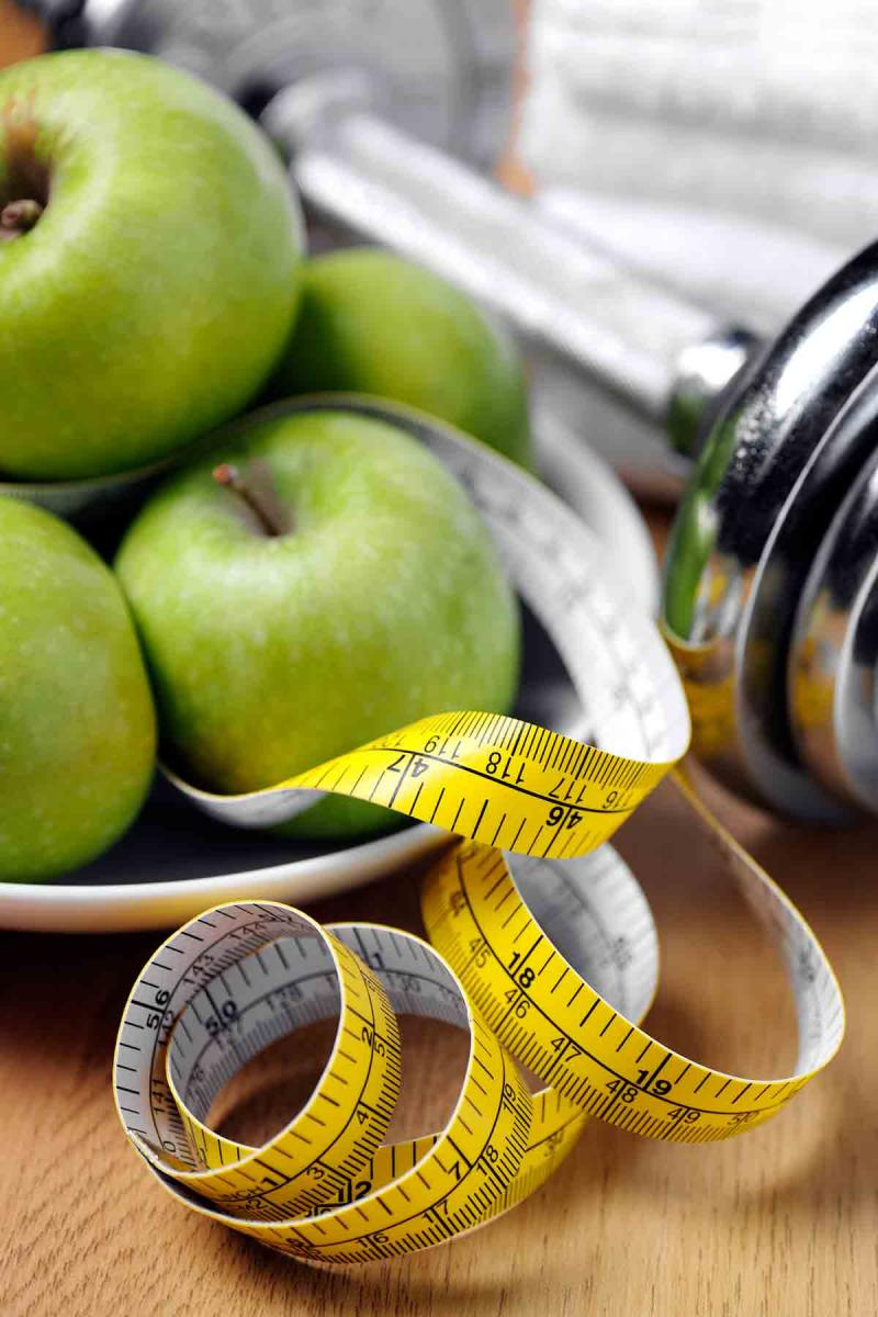 apples, free weights and a tape measure on a tabletop