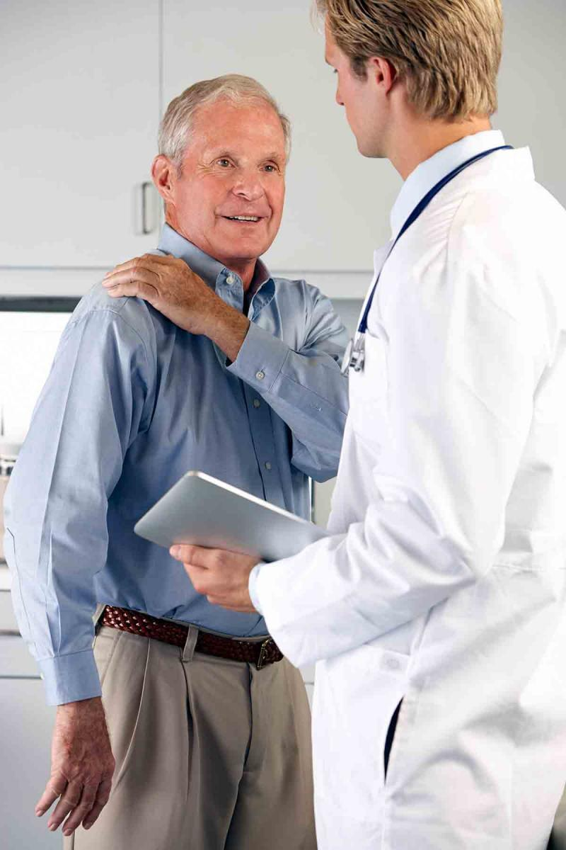 an older male patient shows a male physician the location of his shoulder pain